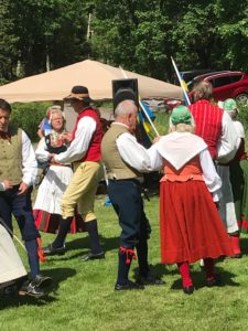 Folk som dansar midsommardans i folkdräkter